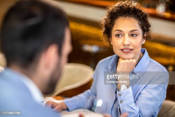 over the shoulder view of a female entrepreneur while she's carefully listening  to her colleague during a meeting - financial analyst stock pictures, royalty-free photos & images
