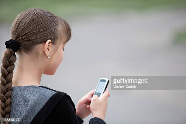 Over the shoulder view of a girl text messaging