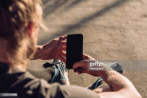 over the shoulder view of a runner using a smartphone outdoors (blank screen, copy space) - looking over shoulder stock pictures, royalty-free photos & images