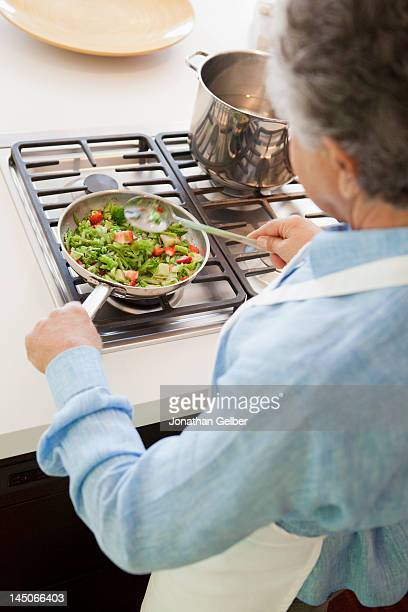 Over the shoulder view of a senior man cooking vegetables