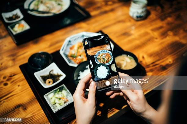 over the shoulder view of a young woman taking photos of freshly served japanese meal set before eating it with smartphone in a restaurant - travel ストックフォトと画像