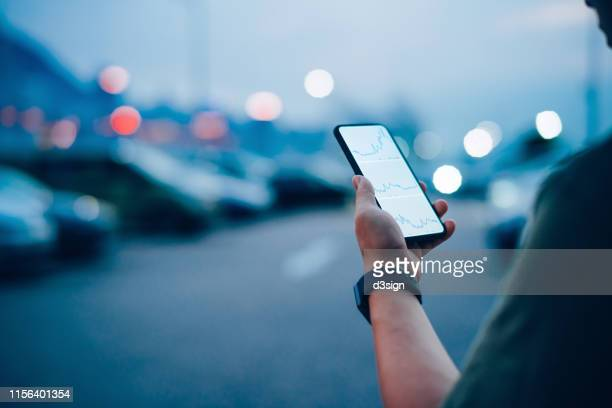over the shoulder view of businessman checking financial trading data on smartphone while walking to his car in the carpark in city - return on investment stock pictures, royalty-free photos & images