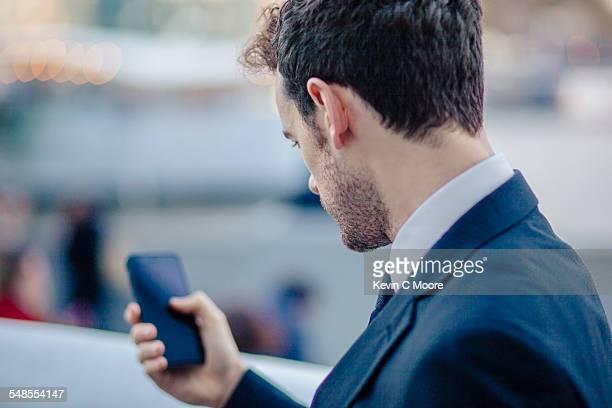 over the shoulder view of businessman texting on smartphone - sobre os ombros - fotografias e filmes do acervo