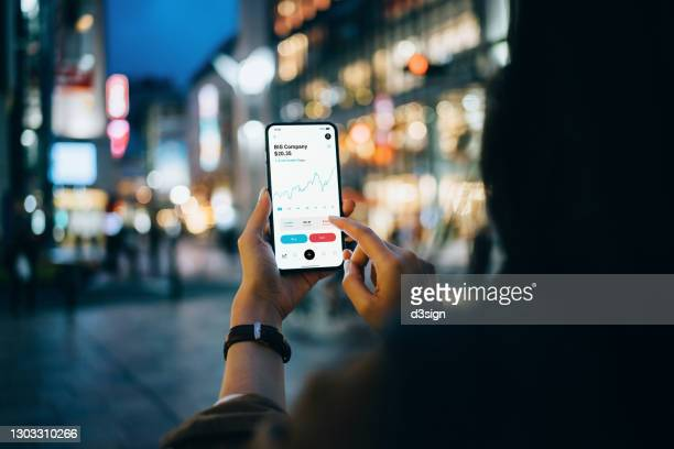 over the shoulder view of businesswoman reading financial stock market analysis on smartphone on the go, in downtown city street against illuminated urban skyscrapers in the evening. business on the go - blockchain stock pictures, royalty-free photos & images