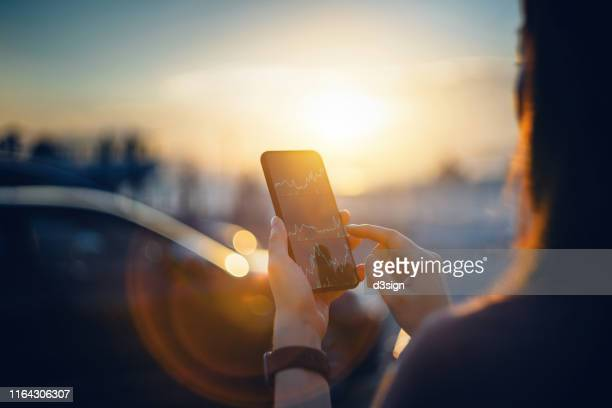 over the shoulder view of businesswoman reading financial trading data on smartphone in the city in front of cars at beautiful sunset with lens flare - bull market stock pictures, royalty-free photos & images