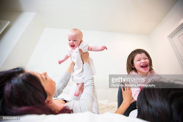 Over the shoulder view of female couple laughing on bed with baby and toddler daughters