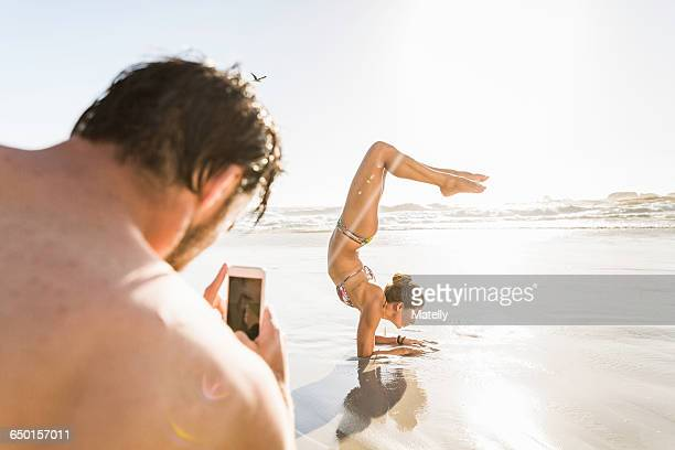 Over the shoulder view of man photographing girlfriend on beach, Cape Town, South Africa