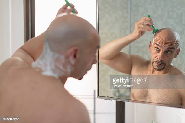 Over the shoulder view of mature man shaving his head in bathroom