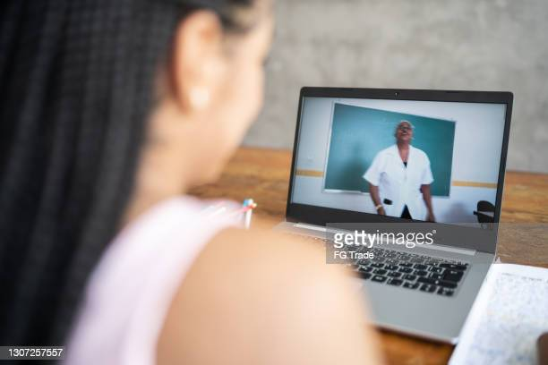 over the shoulder view of teenager girl watching virtual class at home - looking over shoulder stock pictures, royalty-free photos & images
