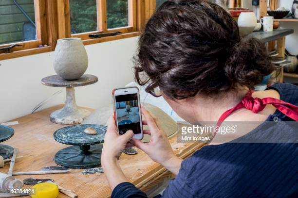 over the shoulder view of woman sitting in her ceramics workshop, checking her mobile phone. - looking over shoulder ストックフォトと画像