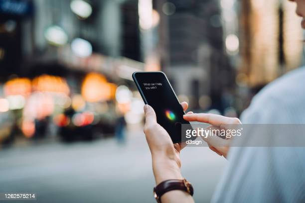 over the shoulder view of young asian businesswoman using ai assistant on smartphone on the go in financial district in the city - intelligence stock pictures, royalty-free photos & images