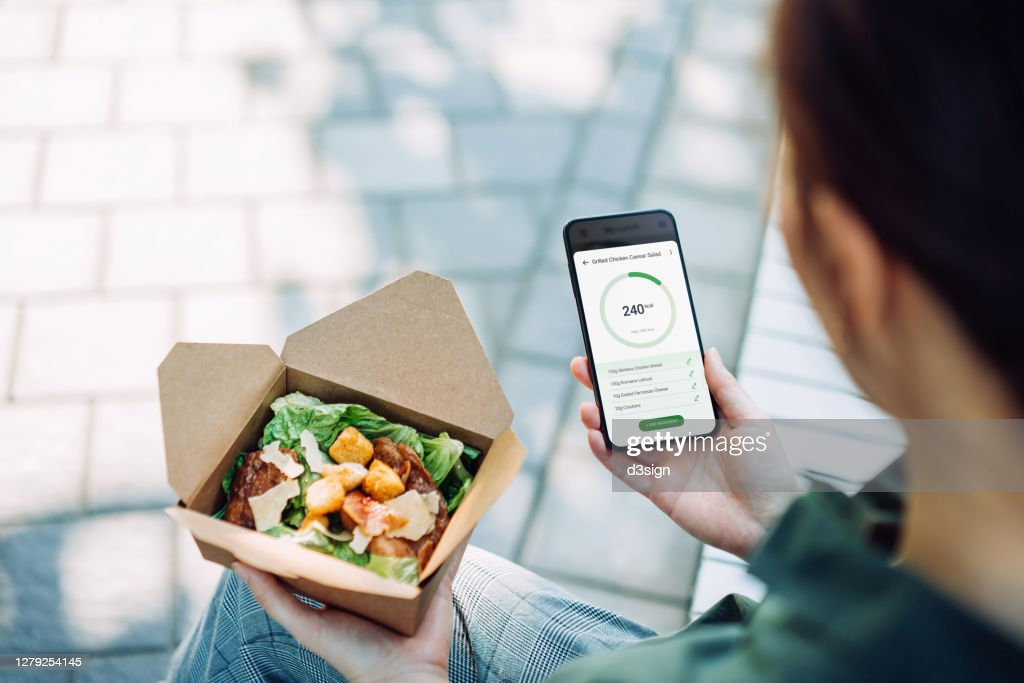 Over the shoulder view of young Asian businesswoman using fitness plan mobile app on smartphone to tailor make her daily diet meal plan, checking the nutrition facts and calories intake of the food while having meal outdoors in an urban park : Stock Photo