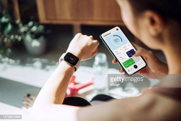 over the shoulder view of young asian sports woman checking pulse on smartwatch and syncing her smartwatch with fitness app on smartphone to monitor her training progress after working out / exercising / practicing yoga at home in the fresh bright morning - スマートウォッチ ストックフォトと画像