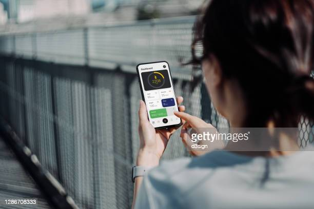 over the shoulder view of young asian sports woman using fitness app on smartphone to monitor her training progress while doing outdoor walk / exercising in the fresh bright morning with shades of sunlight - sports track stock pictures, royalty-free photos & images