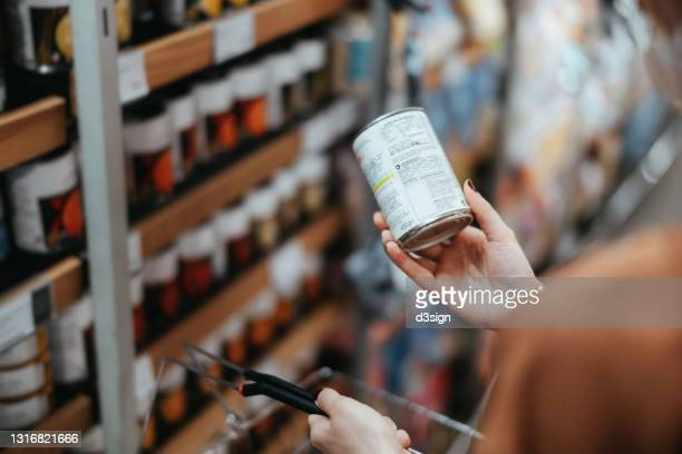 over the shoulder view of young asian woman carrying a shopping basket, grocery shopping in supermarket. holding a tin can and reading the nutritional label at the back - looking over shoulder ストックフォトと画像