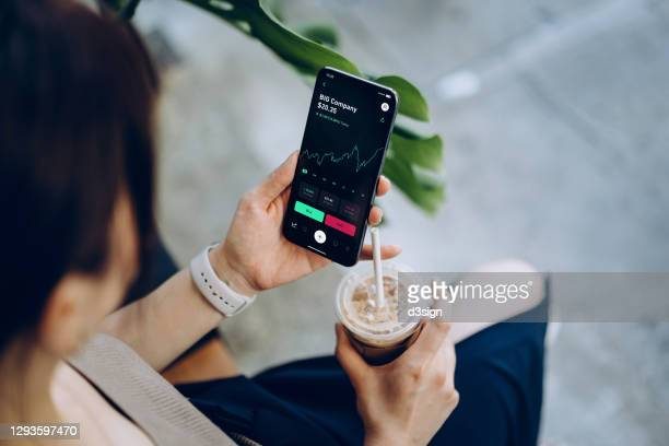 over the shoulder view of young asian woman checking financial trading data with mobile app on smartphone while sitting outdoors in a cafe, drinking coffee. business on the go - stock price stock pictures, royalty-free photos & images