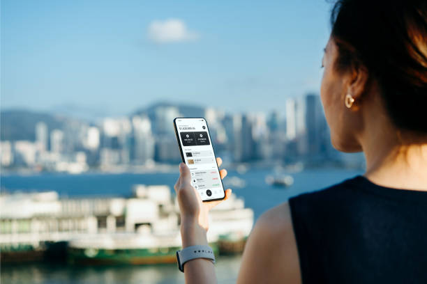 Over the shoulder view of young Asian woman managing online banking with mobile app on smartphone on the go, by the promenade of Victoria harbour with Hong Kong city skyline. Transferring money, paying bills, checking balance. Technology makes life easier