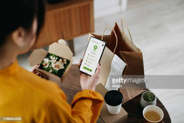 over the shoulder view of young asian woman ordering home delivery takeaway food with mobile app on smartphone, tracking status and confirming the food order. enjoying a box of fresh grilled chicken vegetable salad. technology makes life so much easier - food stock pictures, royalty-free photos & images
