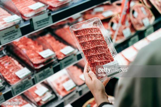 over the shoulder view of young asian woman shopping in a supermarket. she is choosing meat and holding a packet of organic beef in front of the refrigerated section - fleisch stock-fotos und bilder