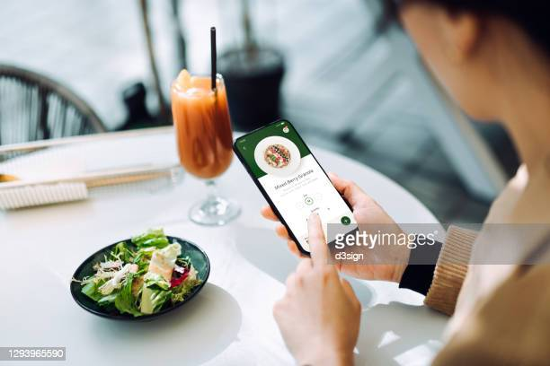 over the shoulder view of young asian woman using mobile app device on smartphone to place a food order in a restaurant. technology makes life so much easier - catering building stock pictures, royalty-free photos & images