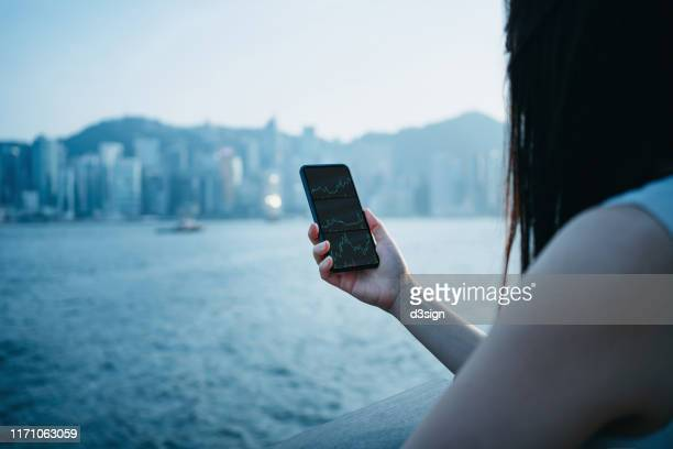 over the shoulder view of young businesswoman checking financial trading data on smartphone by the promenade of victoria harbour against urban city skyline of hong kong - bear market stock pictures, royalty-free photos & images