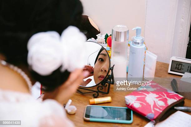 Over the shoulder view of young woman at dressing table applying makeup in mirror