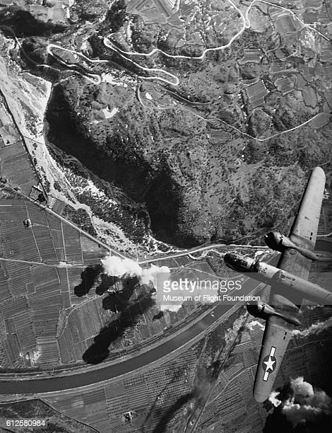 Over the target area during World War II a North American B25J Mitchell bomber drops its payload on the enemy site below