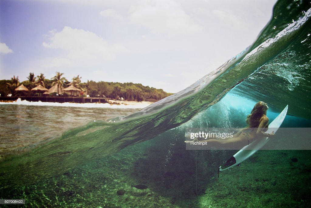 Over under duck dive photo of a surfer girl : Stock Photo