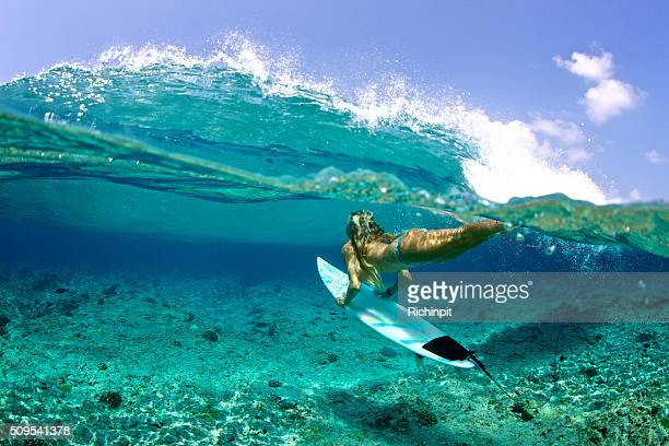 Over under of girl duckdive an oncoming wave