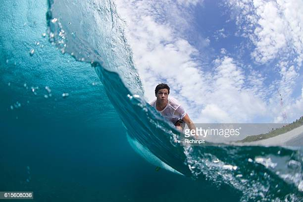 over under split of a surfer on a wave - male maldives stock pictures, royalty-free photos & images