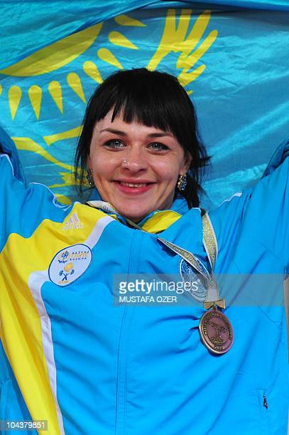 Overall gold medalist and new two world record winner Svetlana Podobedova of Kazhakstan celebrates on the podium after the women's 75kg competition...