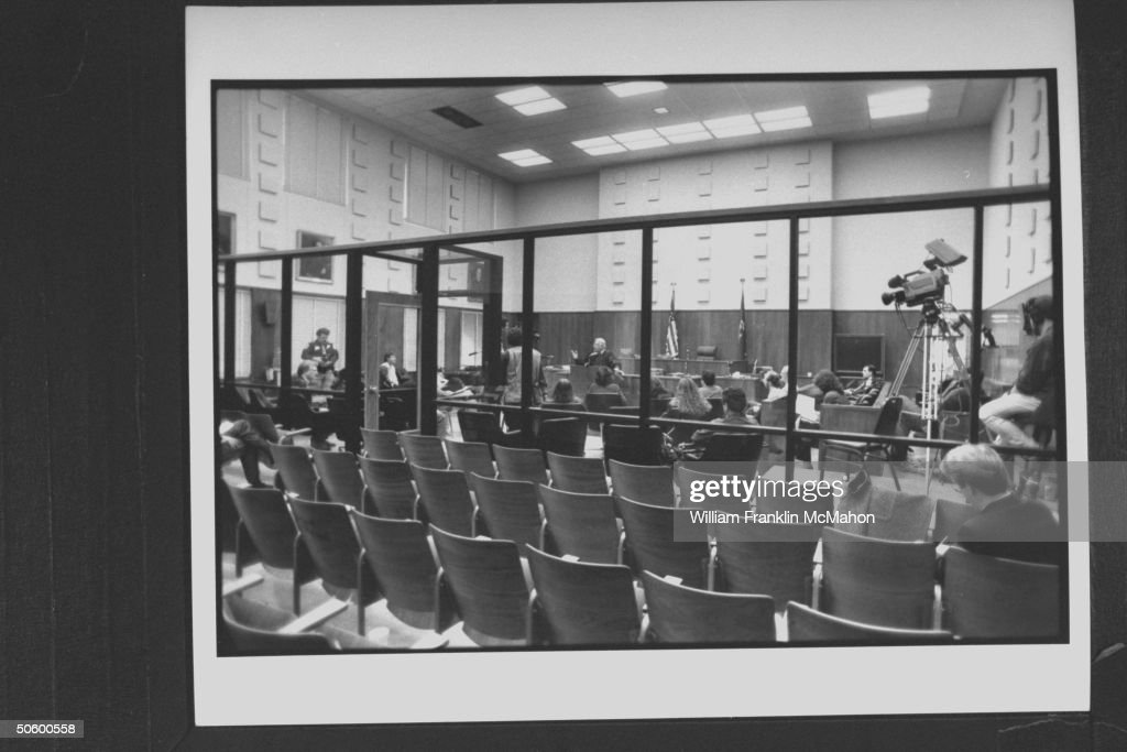 Overall interior view of courtroom w. glass partition separating empty spectators seats fr. trial area in front of the bench where reporters & cameramen are listening to Judge Larry Gram hold a press conference after sentencing serial killer Jeffrey Dahm.er