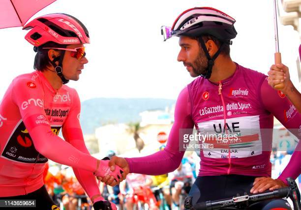 Overall leader and Pink Jersey holder Team Jumbo rider Slovenia's Primoz Roglic shakes hands with Team UAE Emirates rider Colombia's Fernando Gaviria...