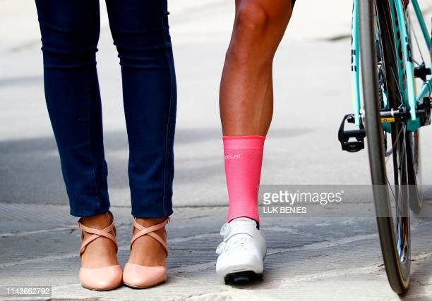 Overall leader and Pink Jersey holder Team Jumbo rider Slovenia's Primoz Roglic leg is seen next to the legs of a hostess ahead of the start of the...