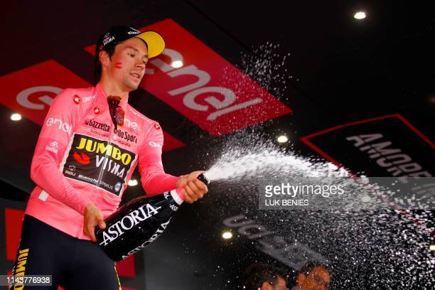 Overall leader and Pink Jersey holder Team Jumbo rider Slovenia's Primoz Roglic sprays champagne on the podium after the fourth stage of the 102nd...