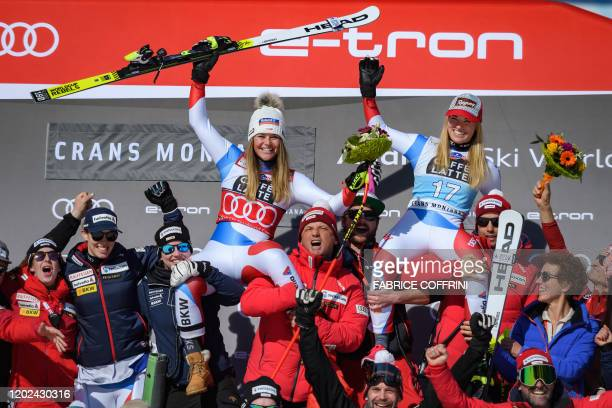 Overall leader Switzerland's Corinne Suter and winner of the race Switzerland's Lara GutBehrami pose with the team during the podium ceremony of the...