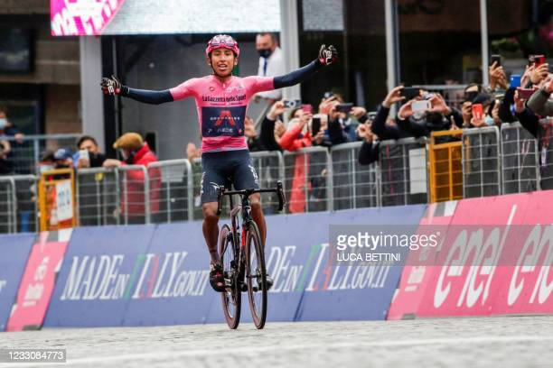 Overall leader Team Ineos rider Colombia's Egan Bernal celebrates as he crosses the finish line to win the 16th stage of the Giro d'Italia 2021...
