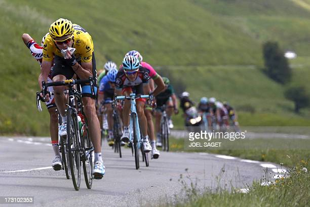 Overall leader's yellow jersey Britain's Christopher Froome eats as he rides during the 168.5 km ninth stage of the 100th edition of the Tour de...
