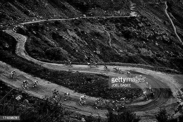 Overall leader's yellow jersey Britain's Christopher Froome rides in the pack in the Col de Sarenne during the 1725 km eighteenth stage of the 100th...