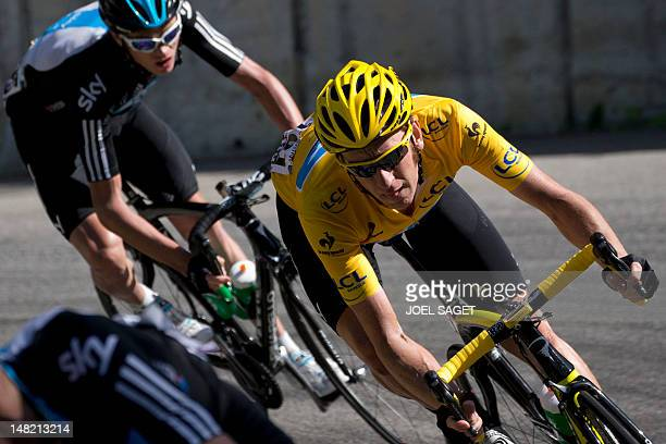 Overall leader's yellow jersey, British Bradley Wiggins and teammate, Great Britain's Christopher Froome speeds in a downhill during the 148 km and...
