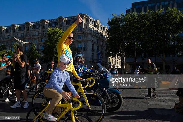 Overall leader's yellow jersey, British Bradley Wiggins, parades with his son at the end of the 120 km and last stage of the 2012 Tour de France...