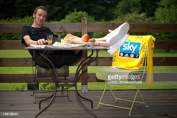 Overall leader's yellow jersey British Bradley Wiggins poses with his jersey as he takes his breakfast at the hotel hosting British Sky cycling team...
