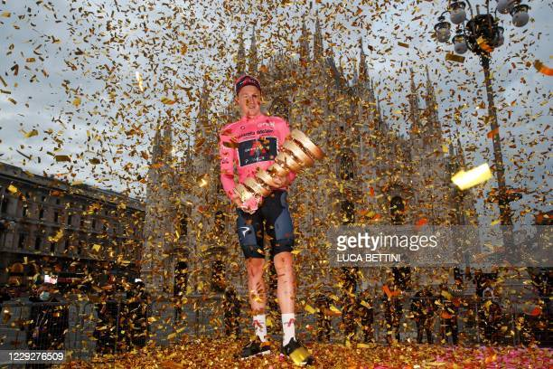"""Overall race winner Team Ineos rider Great Britain's Tao Geoghegan Hart wearing the leader's pink jersey holds the """"Never ending trophy"""" as he..."""