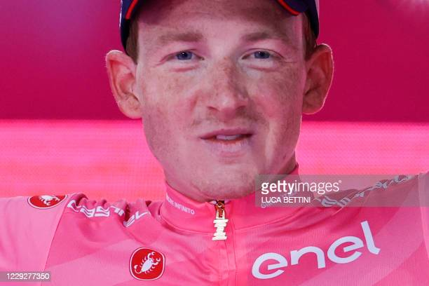 Overall race winner Team Ineos rider Great Britain's Tao Geoghegan Hart wearing the leader's pink jersey celebrates on podium, after the the 21st and...