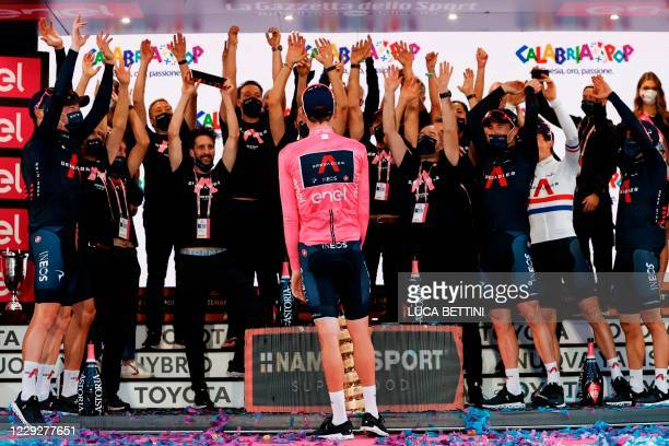 Overall race winner Team Ineos rider Great Britain's Tao Geoghegan Hart wearing the leader's pink jersey celebrates on podium with his teammates...