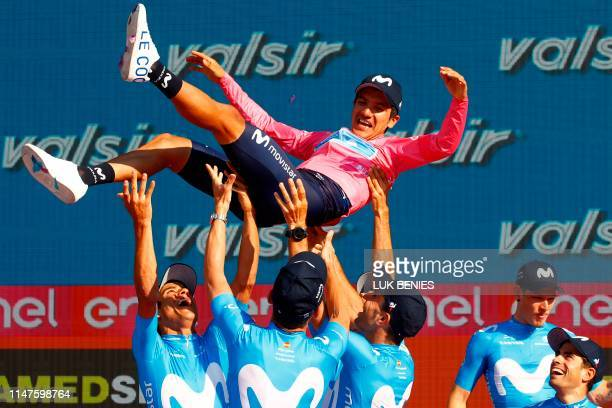 Overall race winner Team Movistar rider Ecuador's Richard Carapaz is thrown in the air by his teammates as they celebrate on the podium after stage...