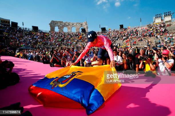 Overall race winner Team Movistar rider Ecuador's Richard Carapaz lays Ecuador's flag to pose with the Never ending trophy during podium ceremonies...