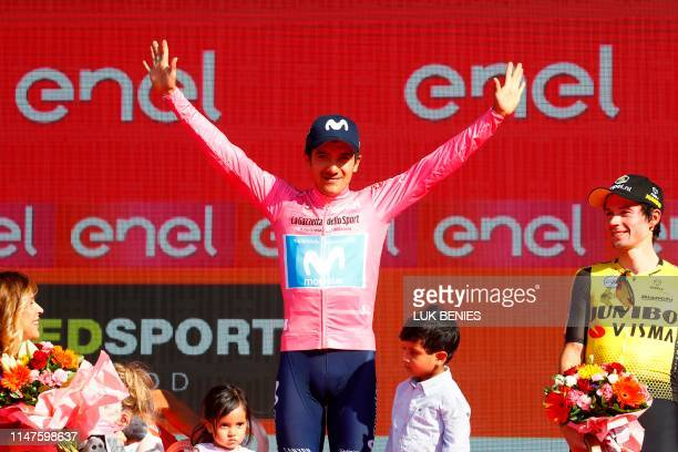 Overall race winner Team Movistar rider Ecuador's Richard Carapaz celebrates on the podium with his children and overall third-placed Team Jumbo...
