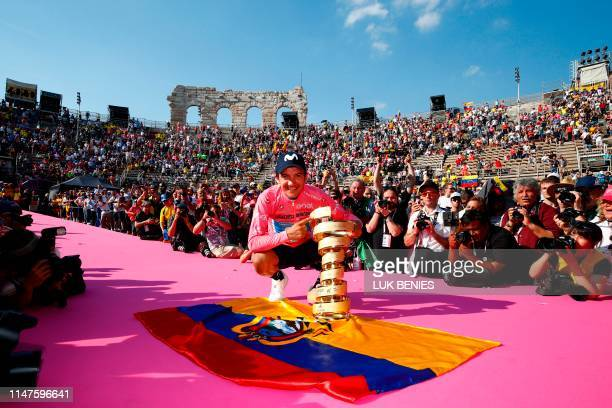 """Overall race winner Team Movistar rider Ecuador's Richard Carapaz poses with the """"Never ending trophy"""" by Ecuador's flag during podium ceremonies in..."""