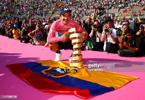 "Overall race winner Team Movistar rider Ecuador's Richard Carapaz poses with the ""Never ending trophy"" by Ecuador's flag during podium ceremonies in..."